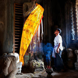 Jo Ann Tomaselli - Angkor Wat Devotee Lights Incense in Buddha Temple