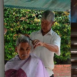 Imran Ahmed - Chinese street side barber cuts client hair Singapore