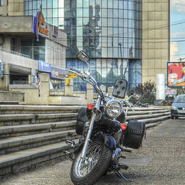 Vlad Baciu - Classic Motorcycle Parked In Front Of A Modern Glass Building