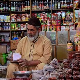 Imran Ahmed - General store keeper tends to paperwork at Empress Market Karachi Pakistan