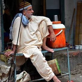 Man sits and relaxes in Lahore walled city Pakistan