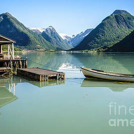 IPics Photography - Reflection of a boat and a boathouse in a fjord in Norway