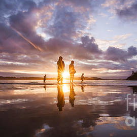Dave Bryson - Reflection of a Family Silhoutted in the Sunset while Playing on the Beach at Low Tide