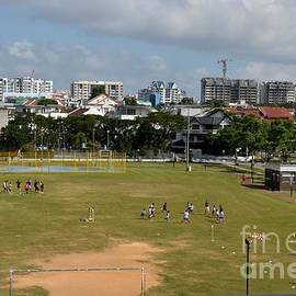 Imran Ahmed - Schoolchildren practicing on playing field with Singapore skyline in background