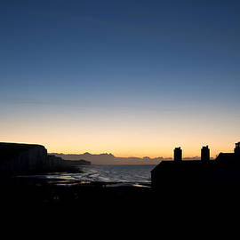 Matthew Gibson - Silhouette of coastguard cottages at Seaford Head at sunrise