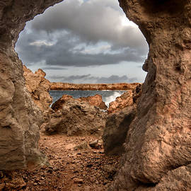 Pedro Cardona - A natural stone arch in north coast of Minorca appears like a pass to One Thousand and One Night