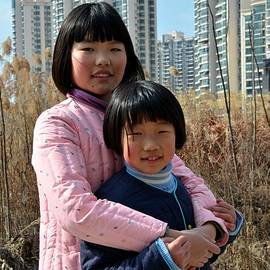 Imran Ahmed - Two Chinese teen sisters hug  and embrace Shanghai China