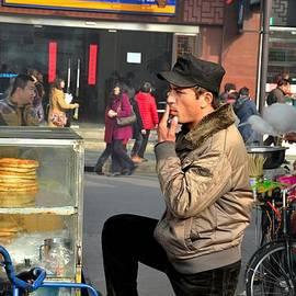 Imran Ahmed - Uighur street side bread vendor smokes Shanghai China