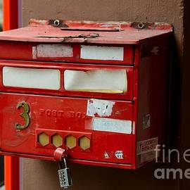 Imran Ahmed - Weathered red post box on pillar with combination lock Singapore