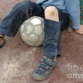 Matthias Hauser - Boy with soccer ball sitting on dirty field