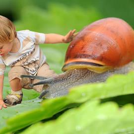 Jaroslaw Grudzinski - Cute tiny boy playing with a snail