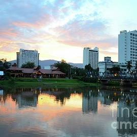 Imran Ahmed - A restaurant and buildings across the Mae Ping River at sunset Chiang Mai Thailand