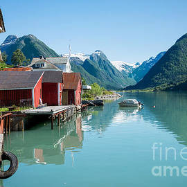 IPics Photography - Boathouse with mountains and reflection in the fjord in Norway