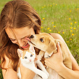 Girl in Field With Kitten and Affectionate Puppy - Susan Schmitz