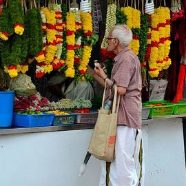 Imran Ahmed - Indian man stands at Little India flower garland shop Singapore