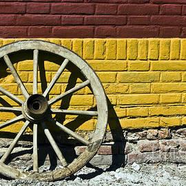 Dan Radi - Old wooden wheel against a wall