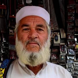 Imran Ahmed - Portrait of Pashtun Pakistani man posing outside belt shop Empress Market Karachi