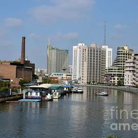 Imran Ahmed - River canal with utility boat chimney and tall buildings Shanghai China