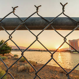 Brian Ball - Summer Sunset Over MGM Lake Looking Through A Fence With Grand Sierra Resort In The Background