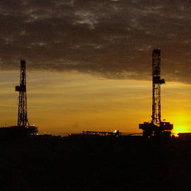 Jeff  Swan - Two oil rigs at sunrise