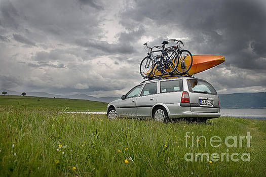 Bicycles and kayak on a car at a lake by Peter Til