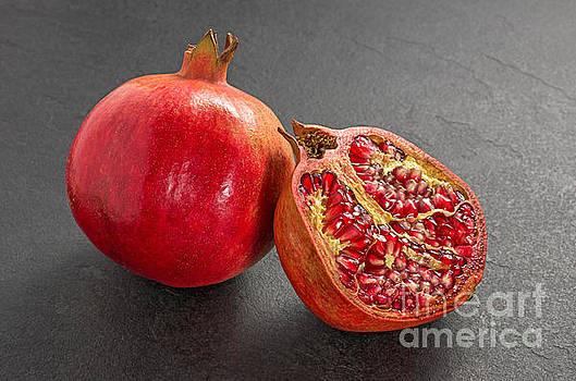 Pomegranate on a slate plate by Palatia Photo