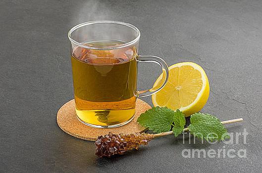 Steaming cup of tea on a slate plate by Palatia Photo