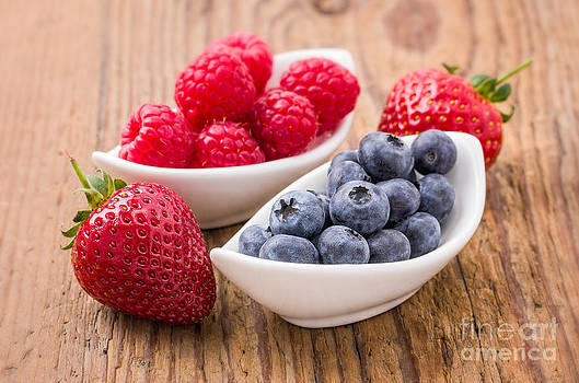 Composition of fresh blueberries raspberries and strawberries by Palatia Photo