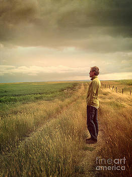 Sandra Cunningham - Man standing on Prairie looking out towards sky