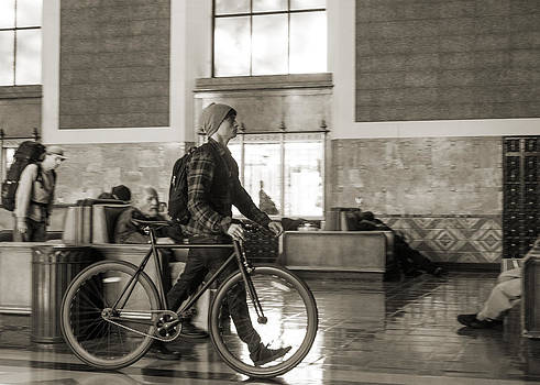 Man walking a bicycle through Union Station in Los Angeles by Kim M Smith