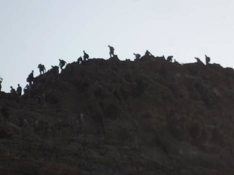 A Line of People Walking on a Mountain by Shea Holliman