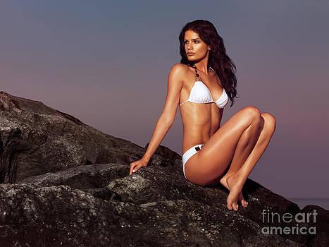 Beautiful woman wearing bikini sitting on rock near water by Oleksiy Maksymenko