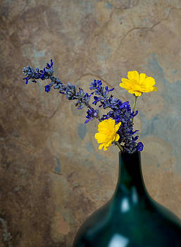 Blue and yelow wildflowers in a turquoise vase against a rustic  by Kim M Smith