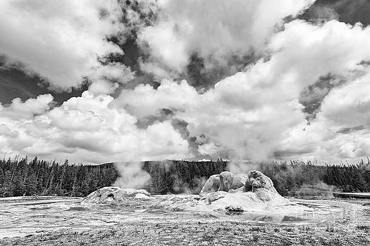 Jamie Pham - Cloud Creators - Twin geysers steaming under a dramatic sky in Yellowstone National Park.