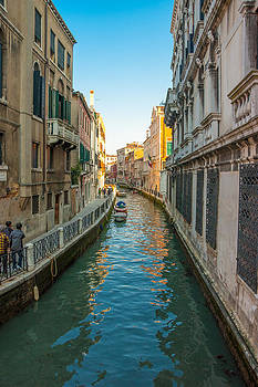 Converging view of Venice buildings along the canal and walkway by Jirawat Cheepsumol