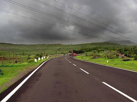 Dark clouds on the highway by Joe Zachariah