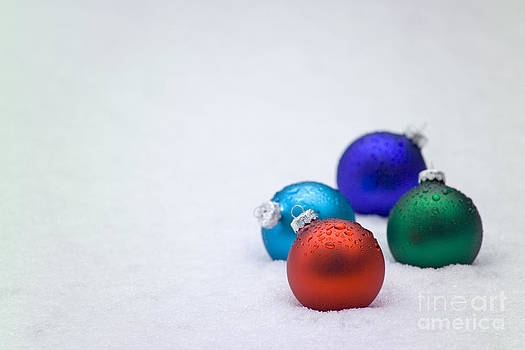 Four Christmas balls in snow by Christopher Campbell