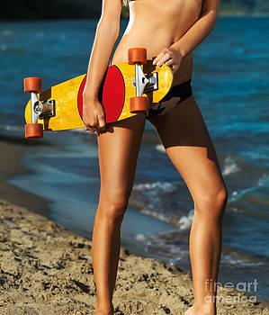 Girl with skateboard on the beach by Oleksiy Maksymenko