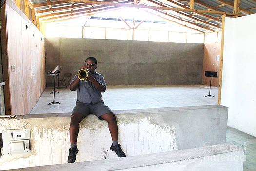 Haitian boy plays trumpet by Jim Wright