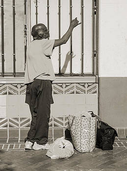 Homeless man reaching up with his hand by Kim M Smith