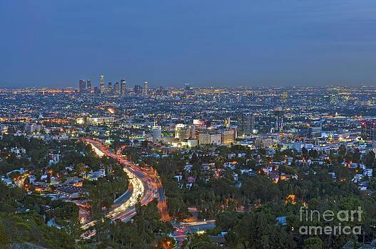 David Zanzinger - LA Skyline at night car tail lights streaking on 101 Freeway
