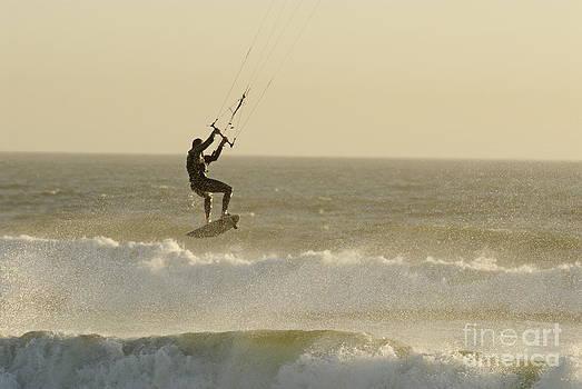 Man kitesurfing on high waves by Sami Sarkis