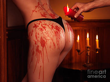 Melted red wax dripping from candle on sexy woman buttocks by Oleksiy Maksymenko