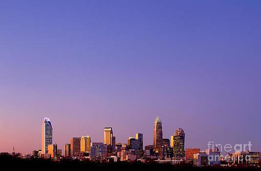 purple skyline Charlotte NC in distance by Patrick Schneider