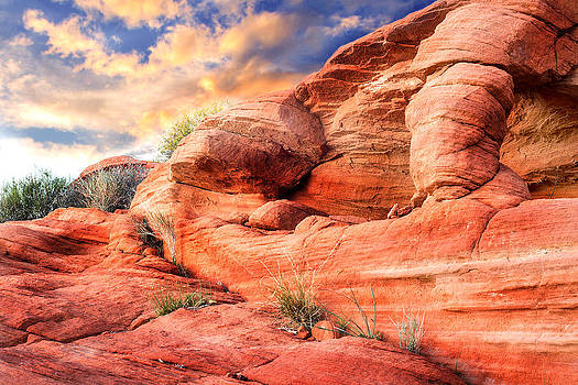 Red rock sculpture with sunset in background by Kim M Smith
