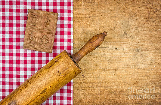 Rolling pin with mold on a wooden board with a checkered tablecloth by Palatia Photo