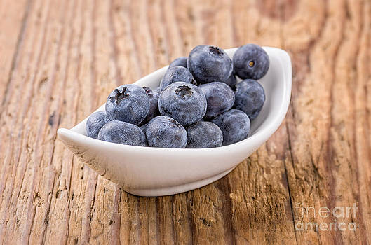 Small bowl filled with fresh blueberries by Palatia Photo
