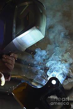 Welder in mask working on steel by Sami Sarkis