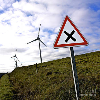 BERNARD JAUBERT - Wind turbines on the edge of a field with a road sign in foreground.