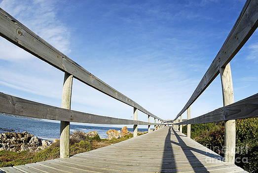 Wooden footbridge by ocean by Sami Sarkis